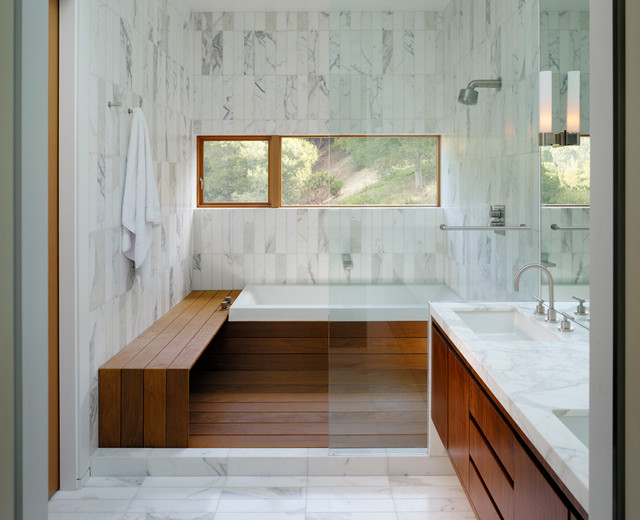 White Marble Bathroom With Window For Light And Wood Bench