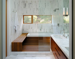White marble bathroom with window for light and wood bench in the shower contemporary-bathroom
