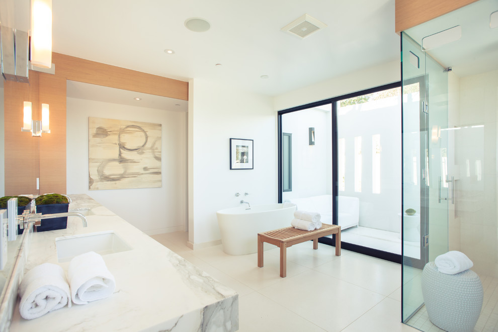 Bathroom - huge contemporary master beige tile and porcelain tile limestone floor bathroom idea in Los Angeles with an undermount sink, flat-panel cabinets, medium tone wood cabinets, marble countertops, a one-piece toilet and white walls