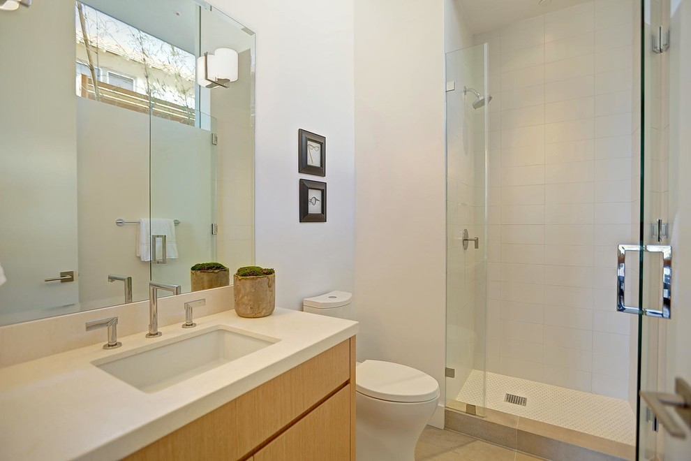 Mid-sized minimalist kids' white tile and ceramic tile ceramic tile alcove shower photo in Los Angeles with an undermount sink, flat-panel cabinets, medium tone wood cabinets, limestone countertops, a one-piece toilet and white walls