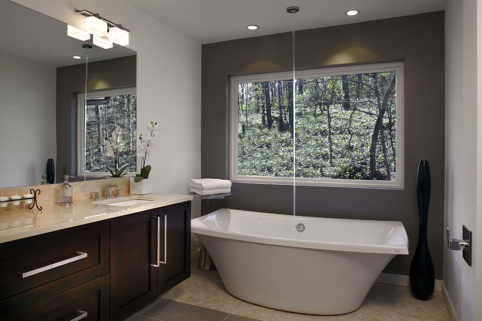 Inspiration for a modern beige tile freestanding bathtub remodel in Atlanta with an undermount sink, shaker cabinets and dark wood cabinets