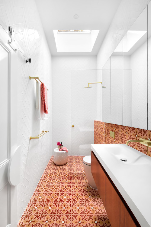 red and orange floor tile in all white bathroom