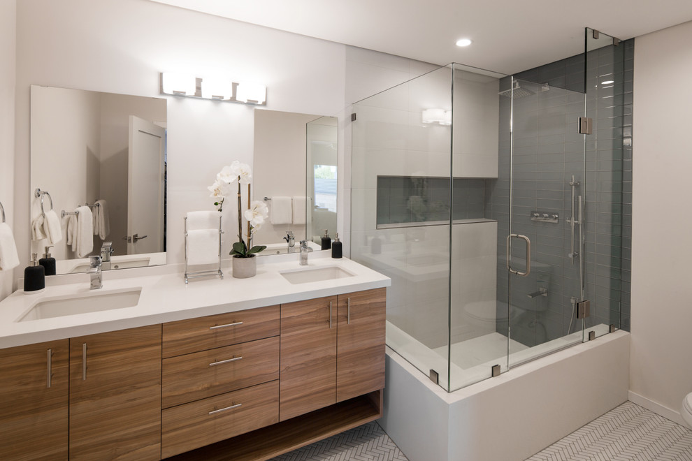 Corner shower - large contemporary 3/4 gray tile and porcelain tile porcelain tile and white floor corner shower idea in Los Angeles with flat-panel cabinets, medium tone wood cabinets, white walls, an undermount sink, quartz countertops and a hinged shower door