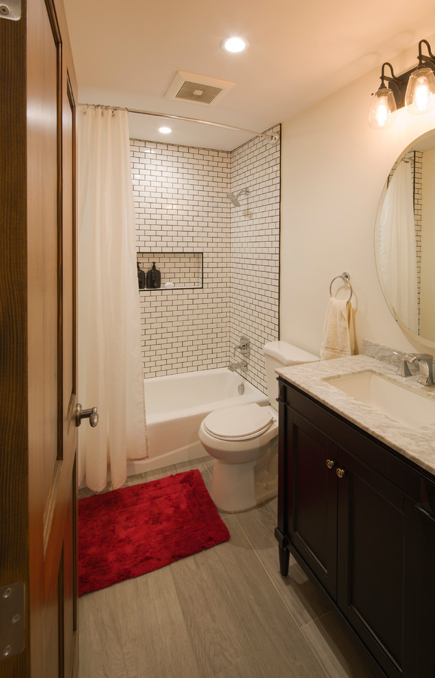 Inspiration for a mid-sized transitional 3/4 white tile and subway tile porcelain tile bathroom remodel in Los Angeles with shaker cabinets, black cabinets, a two-piece toilet, beige walls, an undermount sink and marble countertops