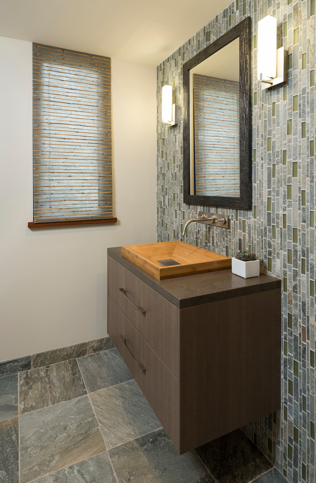 Bathroom - mid-sized modern 3/4 blue tile, gray tile, green tile and matchstick tile slate floor and gray floor bathroom idea in San Diego with flat-panel cabinets, medium tone wood cabinets, a two-piece toilet, beige walls, a trough sink and solid surface countertops