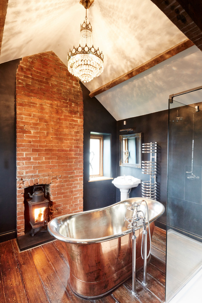 Mid-sized cottage master medium tone wood floor freestanding bathtub photo in Wiltshire with a pedestal sink, a wall-mount toilet and black walls
