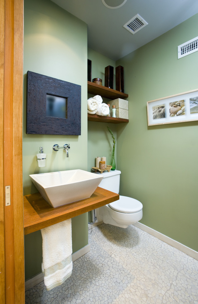Example of a trendy pebble tile floor bathroom design in Los Angeles with a vessel sink and green walls
