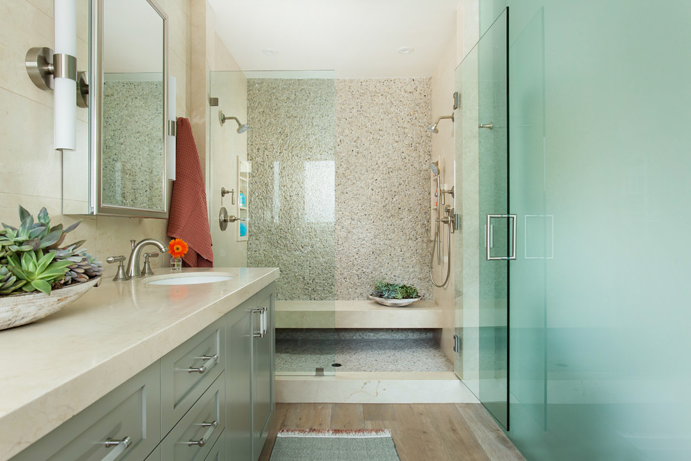 Inspiration for a large coastal master beige tile and marble tile light wood floor and gray floor bathroom remodel in Los Angeles with shaker cabinets, green cabinets, a bidet, beige walls, a drop-in sink, marble countertops and a hinged shower door
