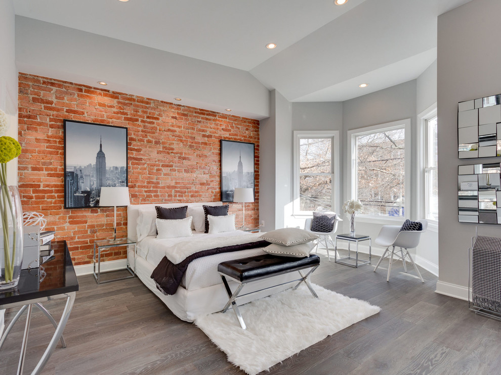 Example of a large trendy master medium tone wood floor and brown floor bedroom design in New York with gray walls and no fireplace