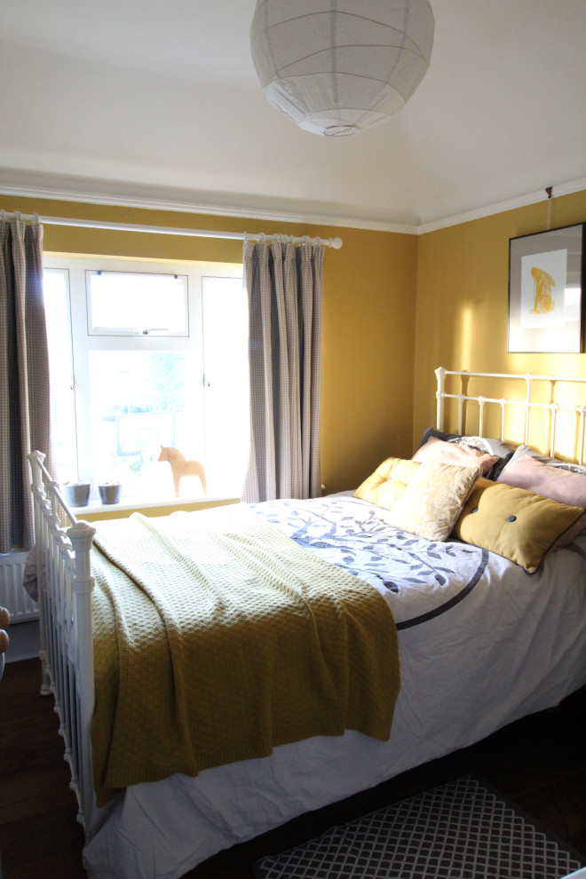 Example of a small danish guest dark wood floor bedroom design in Cambridgeshire with yellow walls, a standard fireplace and a tile fireplace