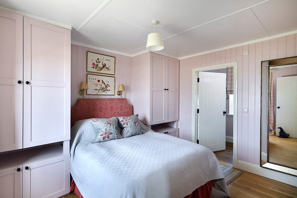 Mid-sized country light wood floor and brown floor bedroom photo in Other with pink walls