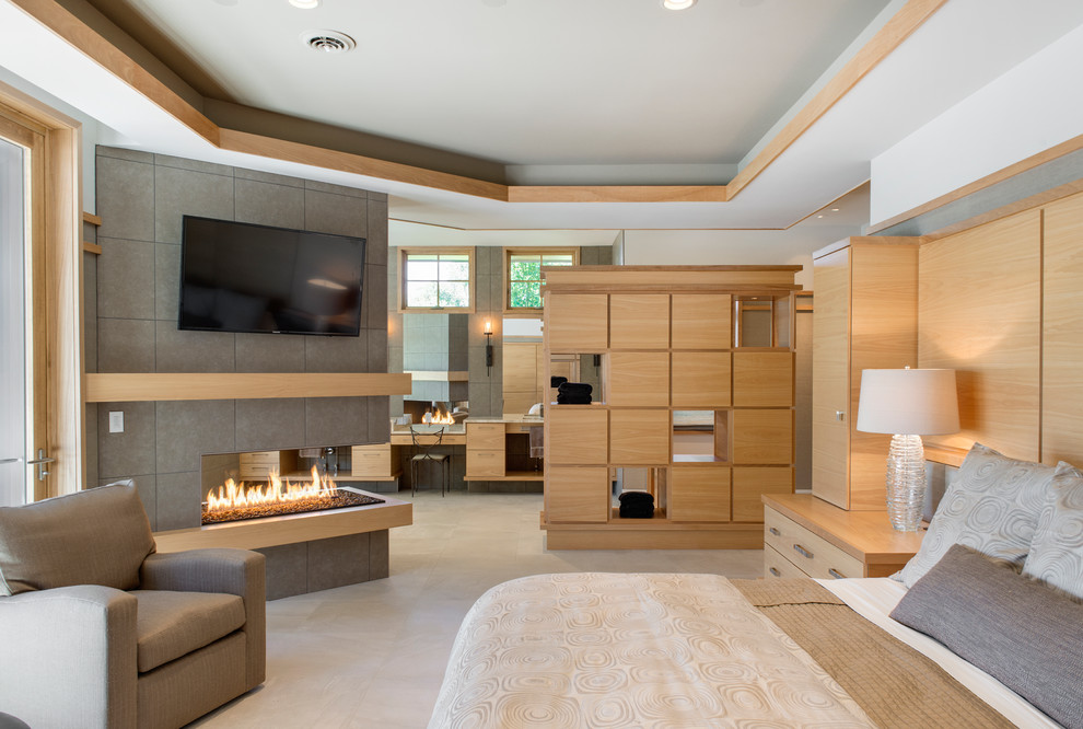 Example of a large trendy master porcelain tile bedroom design in Minneapolis with white walls, a tile fireplace and a two-sided fireplace