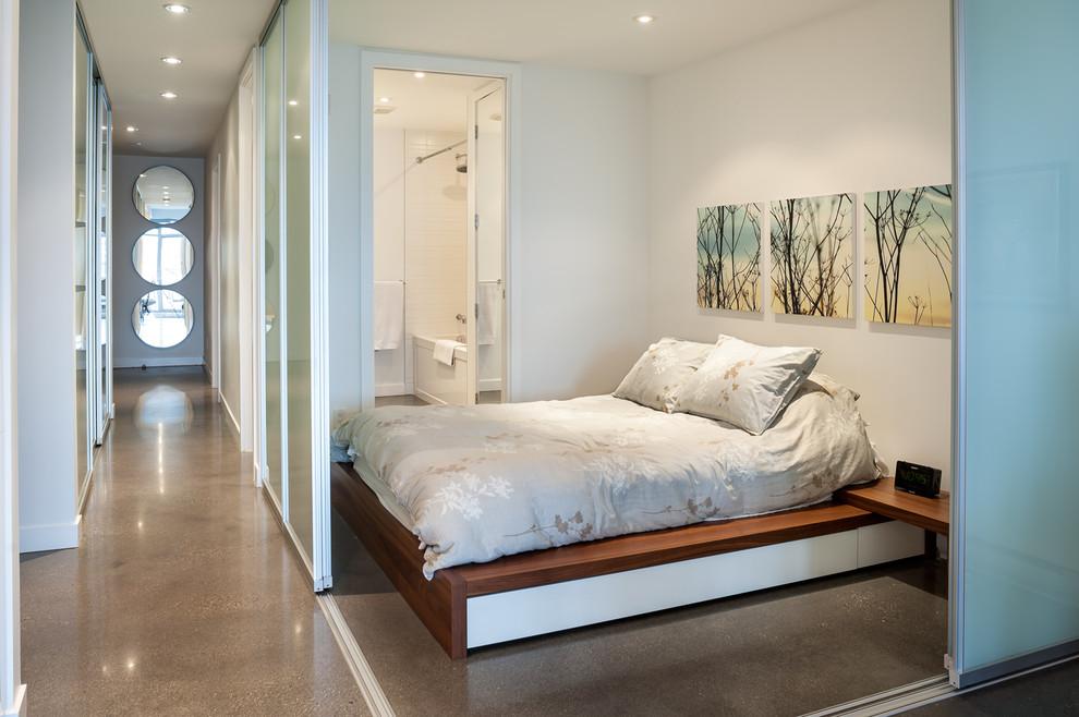 Trendy concrete floor bedroom photo in Vancouver with white walls