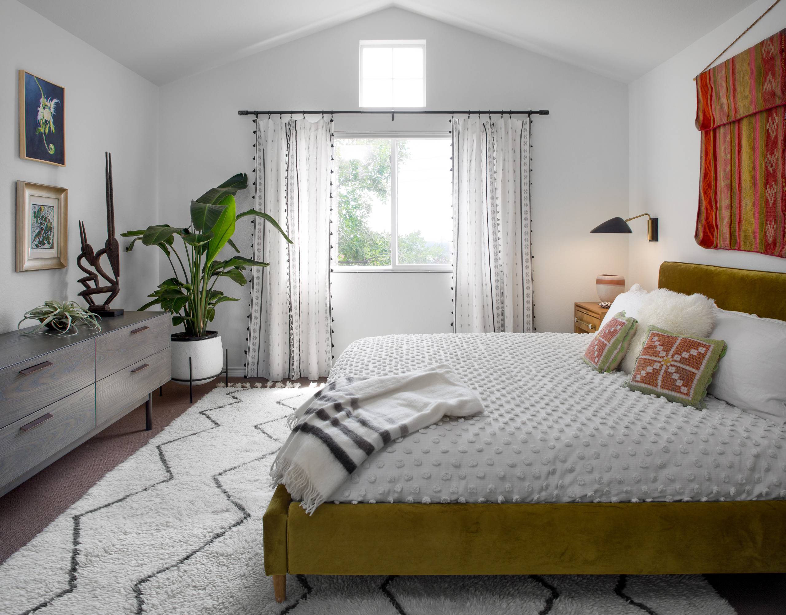 Ah, the bedroom! With our tight budget, we opted to keep the original berber carpet and add an area rug. We ordered the chartreuse velvet bed from Interior Define. The coverlet is from Urban Outfitter