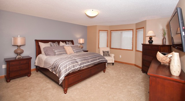 Example of a large classic master carpeted bedroom design in Other with beige walls