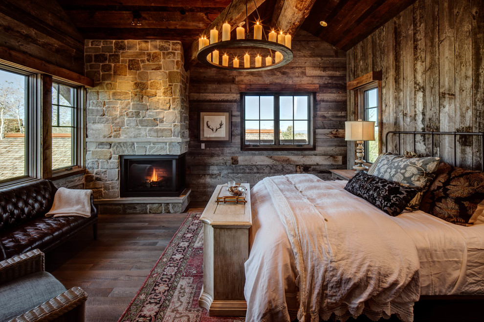 Large mountain style master dark wood floor bedroom photo in Salt Lake City with a corner fireplace and a stone fireplace