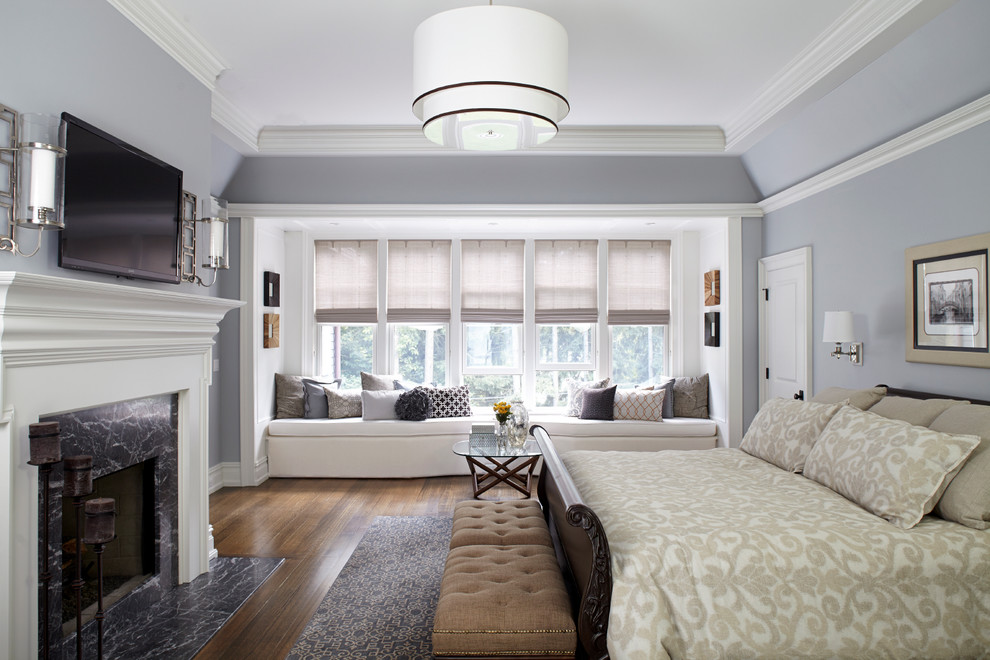 Example of a large classic master medium tone wood floor bedroom design in New York with gray walls and a standard fireplace