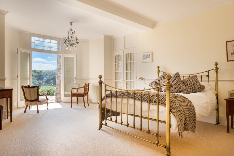 Large cottage master carpeted bedroom photo in Devon with beige walls