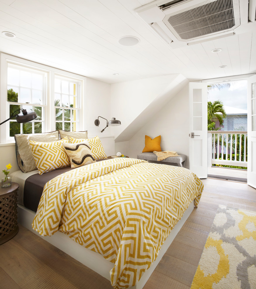 Example of a beach style master light wood floor and beige floor bedroom design in Other with white walls