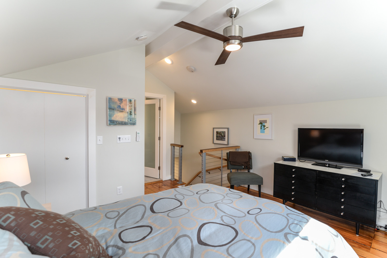 The staircase leads directly to the master bedroom area, with an attached bathroom shown in the background. Although smaller in scale, the overall feel is open and airy with plenty of storage in the u