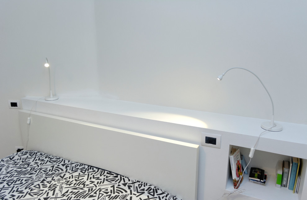 Example of a small trendy master light wood floor bedroom design in Milan with white walls