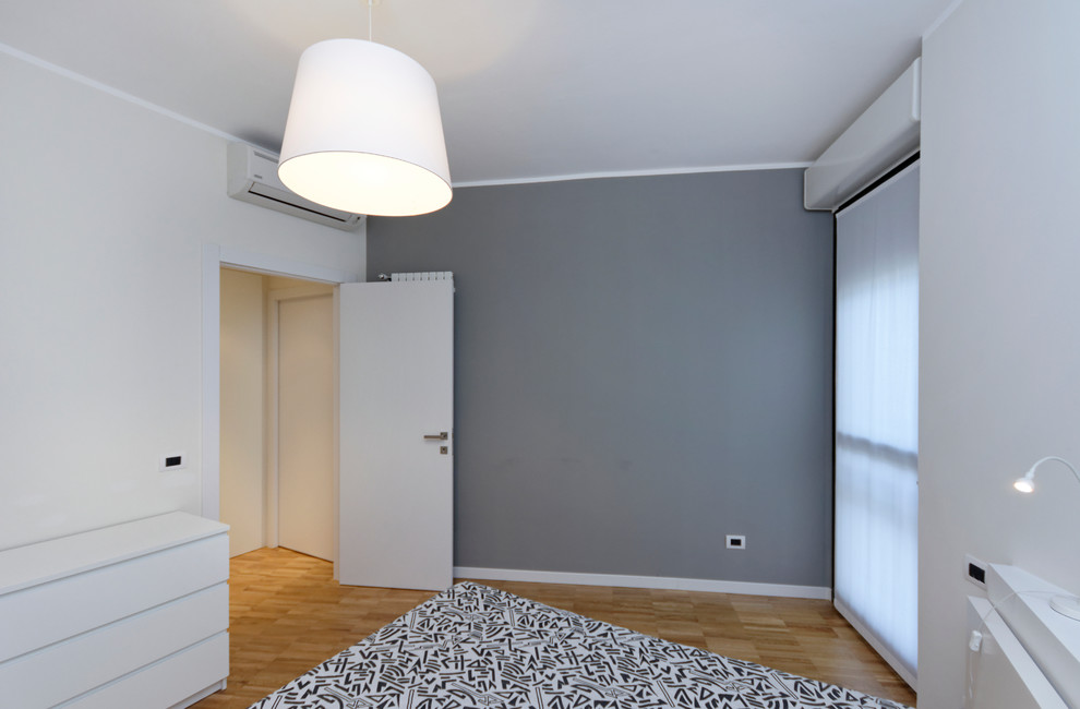 Small trendy master light wood floor bedroom photo in Milan with white walls