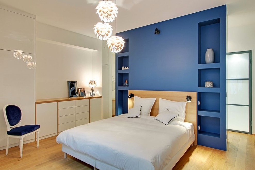 Bedroom - large contemporary master medium tone wood floor bedroom idea in Other with blue walls and no fireplace