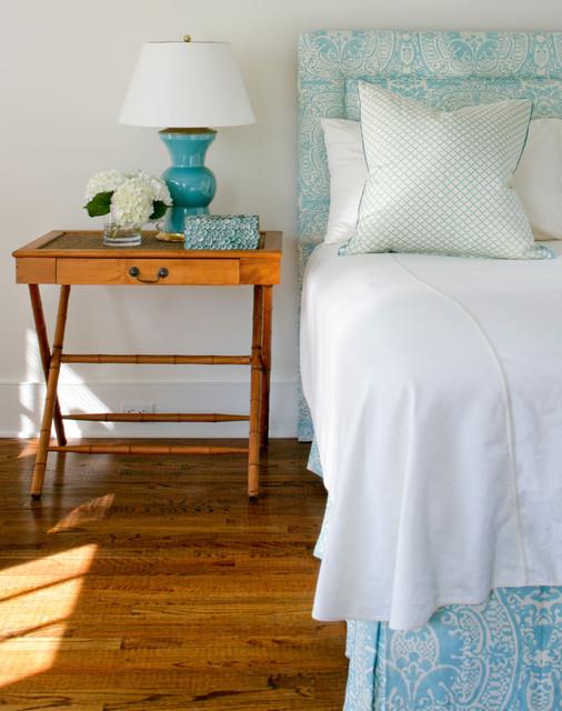 Elegant medium tone wood floor bedroom photo in New York with white walls