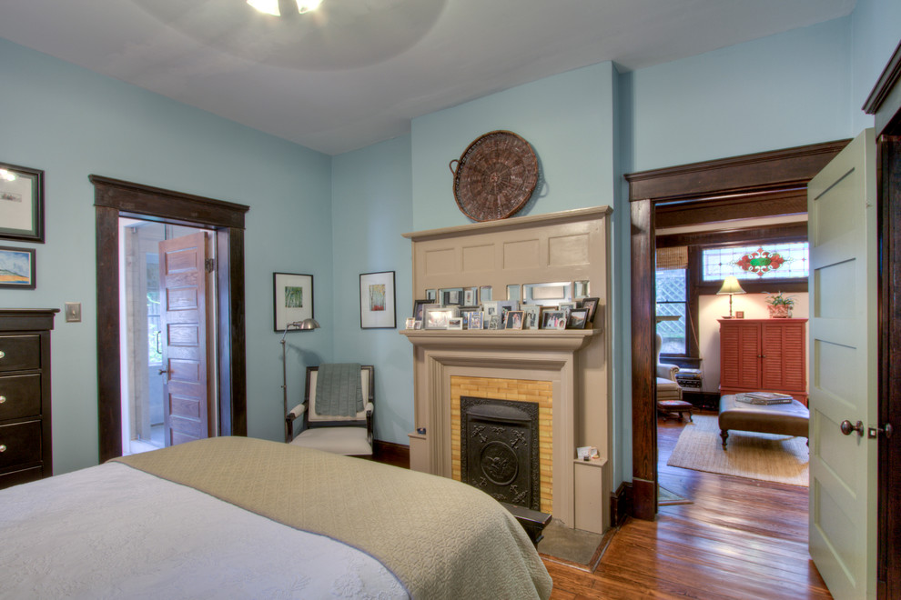 Arts and crafts medium tone wood floor bedroom photo in Atlanta with blue walls, a standard fireplace and a tile fireplace