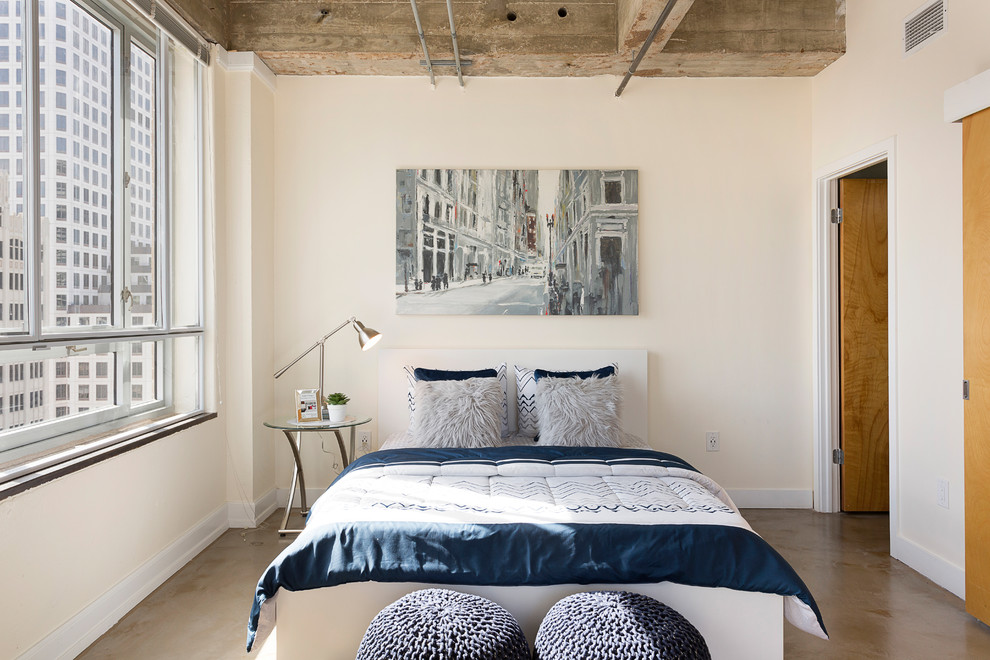 Example of a small urban concrete floor bedroom design in Austin with beige walls and no fireplace