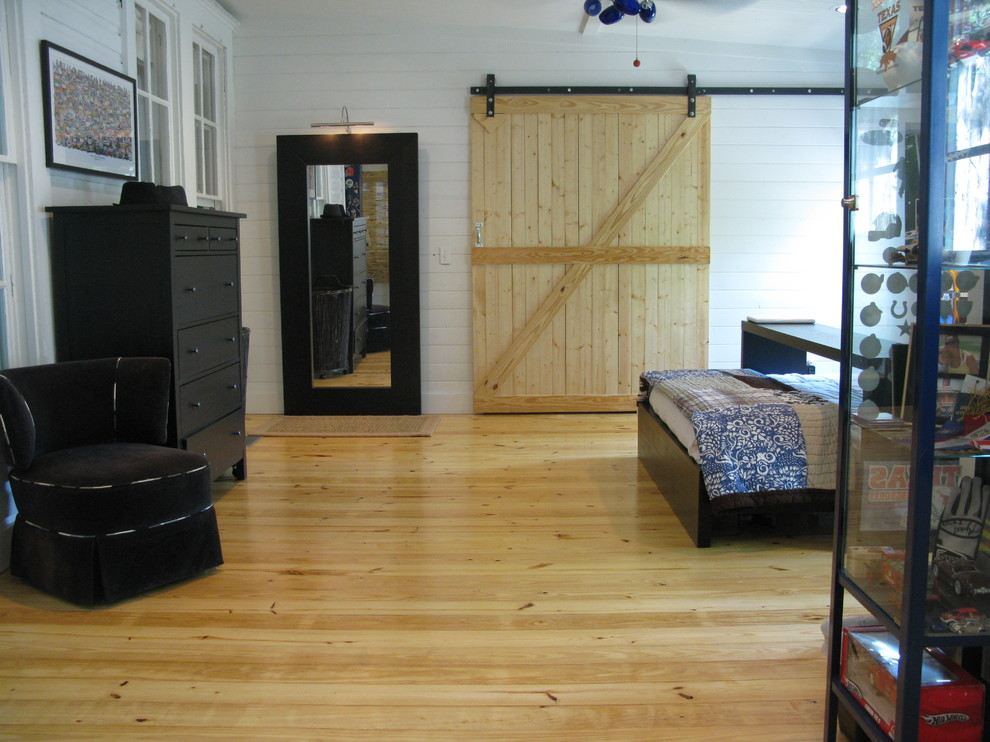 Example of an eclectic medium tone wood floor bedroom design in Austin with white walls