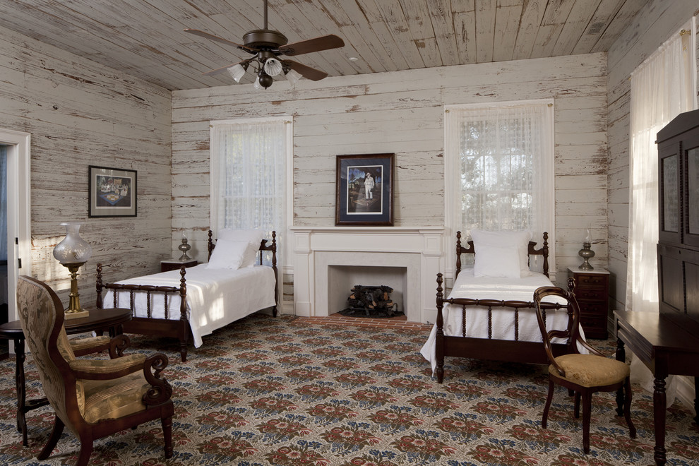 Example of a country guest bedroom design in Austin with a standard fireplace and white walls