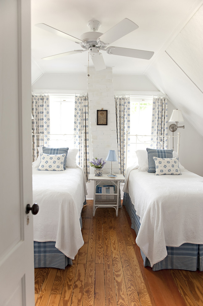 Example of a mid-sized beach style guest medium tone wood floor bedroom design in New York with white walls and no fireplace