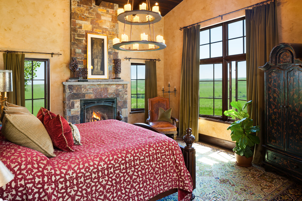 Inspiration for a southwestern master bedroom remodel in Other with orange walls, a standard fireplace and a stone fireplace