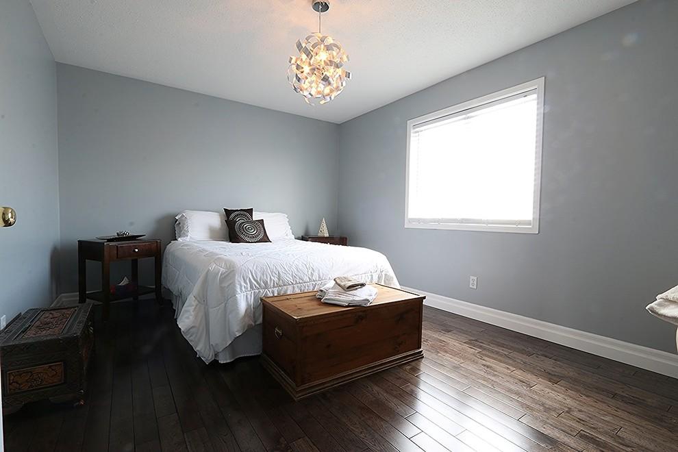 Mid-sized minimalist guest dark wood floor bedroom photo in Ottawa with gray walls