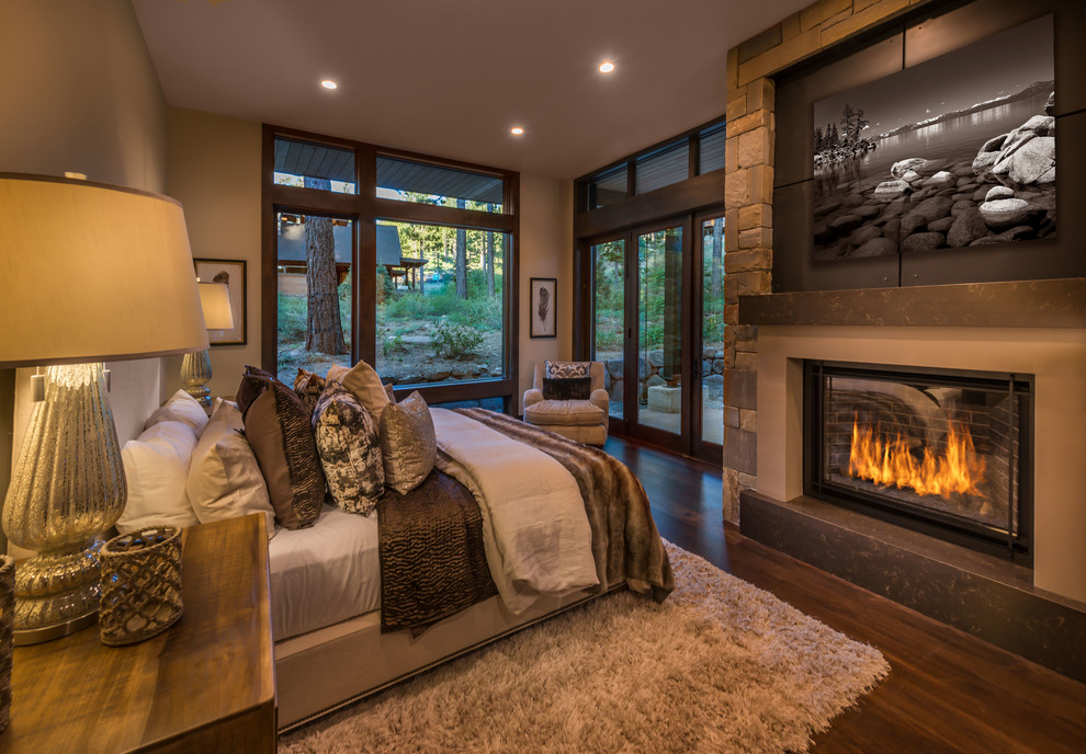 Mountain style dark wood floor and brown floor bedroom photo in Other with beige walls and a standard fireplace