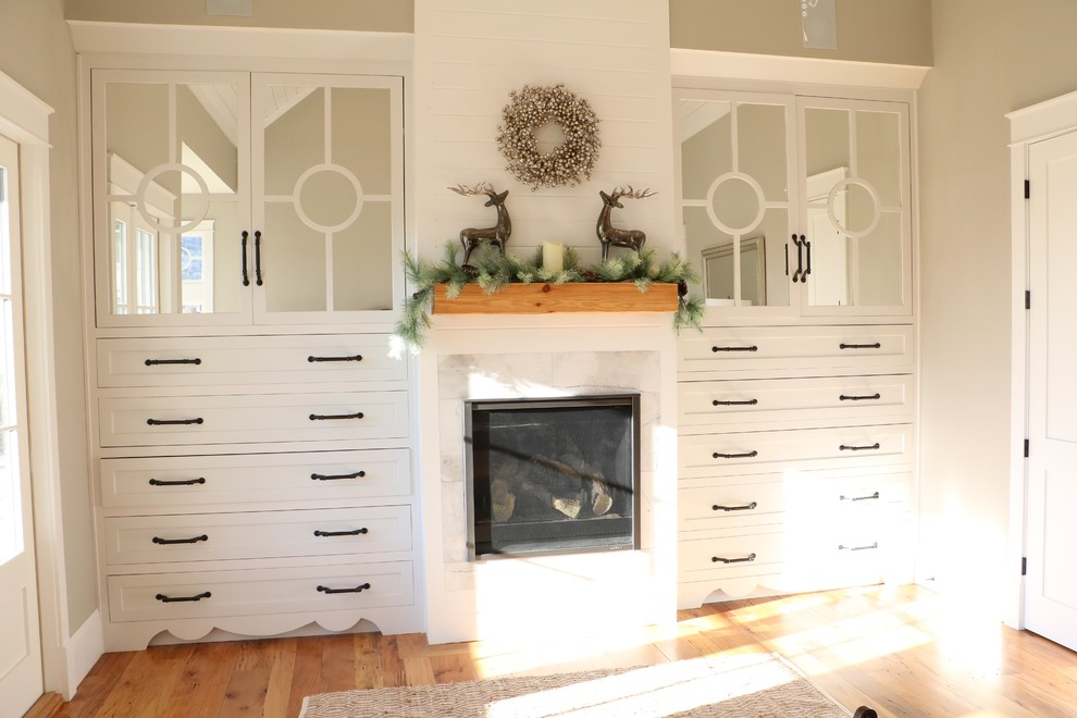 Bedroom - large cottage master medium tone wood floor bedroom idea in Other with gray walls, a standard fireplace and a wood fireplace surround