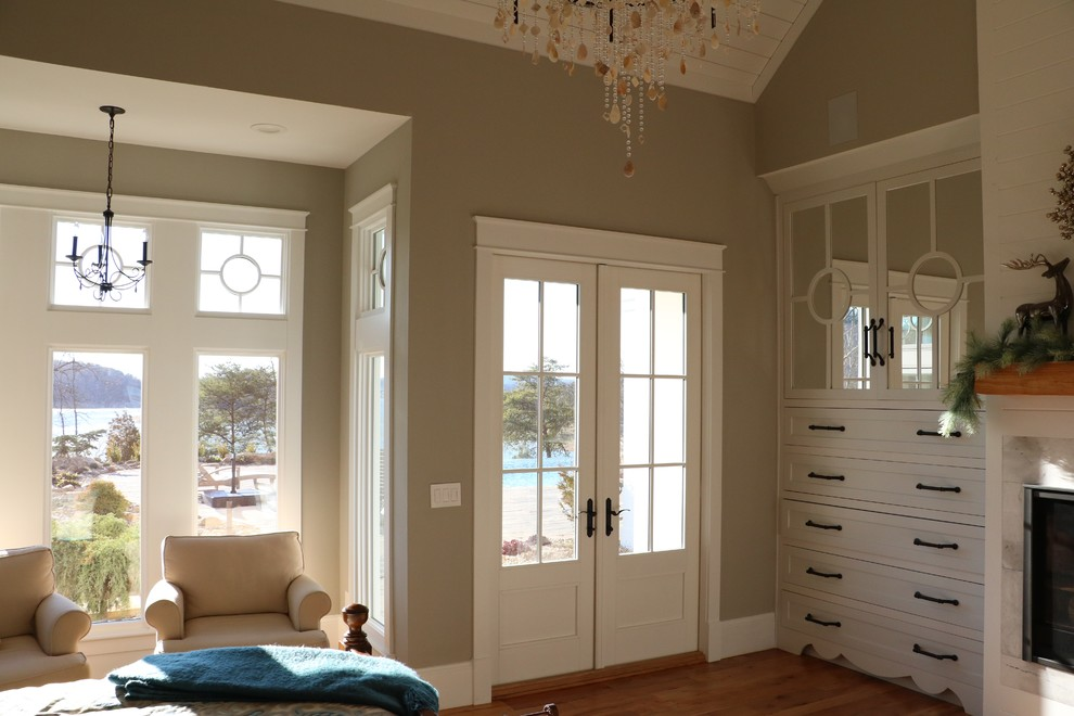 Large cottage master medium tone wood floor bedroom photo in Other with gray walls, a standard fireplace and a wood fireplace surround