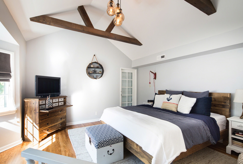 Small beach style loft-style medium tone wood floor bedroom photo in Los Angeles with gray walls and no fireplace