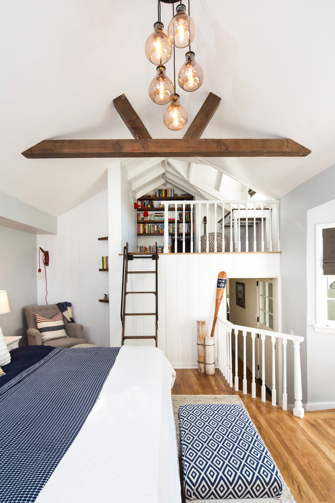 Example of a small beach style loft-style medium tone wood floor bedroom design in Los Angeles with gray walls and no fireplace