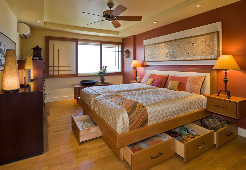 Example of an asian medium tone wood floor bedroom design in Hawaii with orange walls