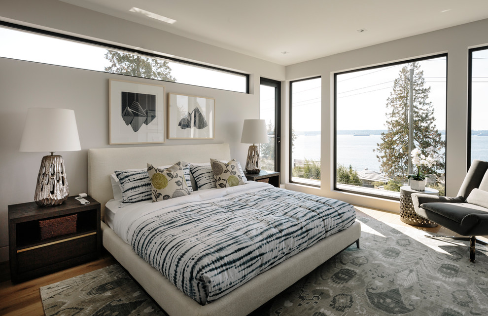 Large trendy master medium tone wood floor and brown floor bedroom photo in Vancouver with white walls