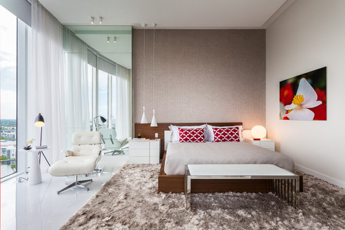 modern penthouse bedroom with large brown shaggy rug