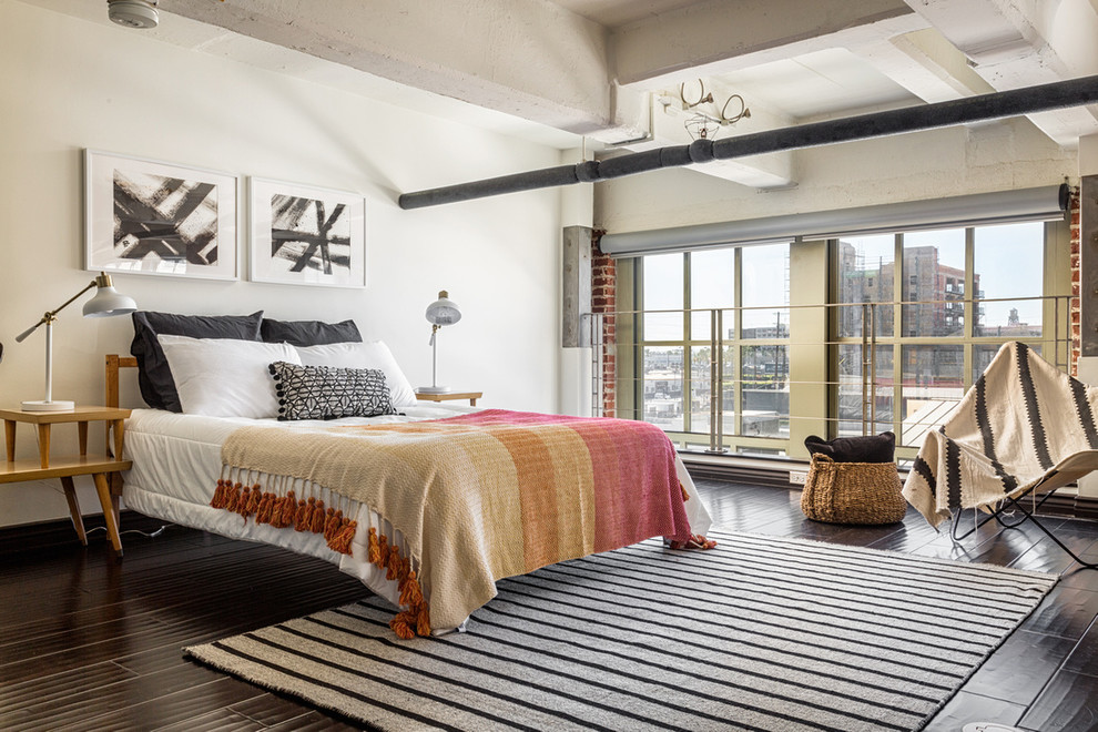 Urban dark wood floor and brown floor bedroom photo in Los Angeles with white walls