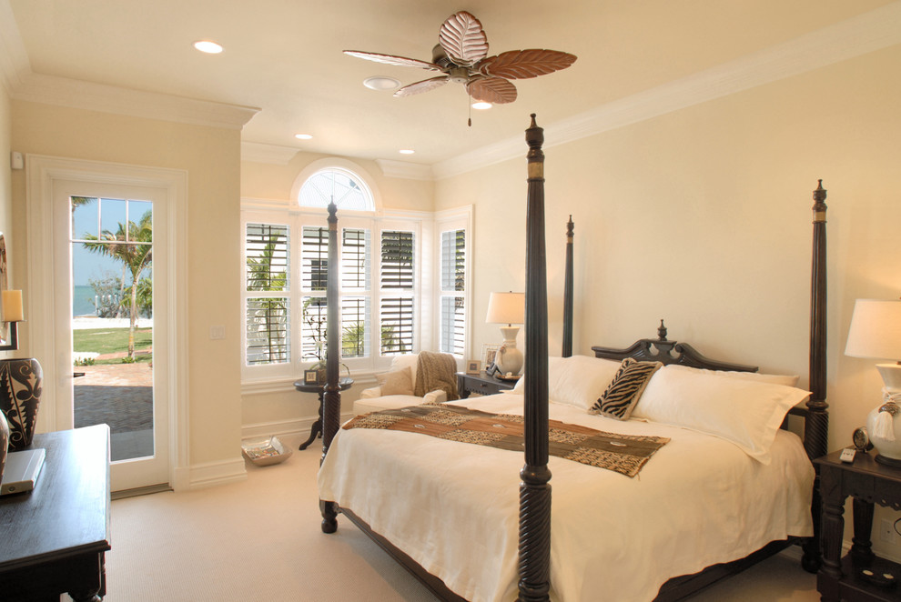 Inspiration for a tropical carpeted bedroom remodel in Miami with beige walls