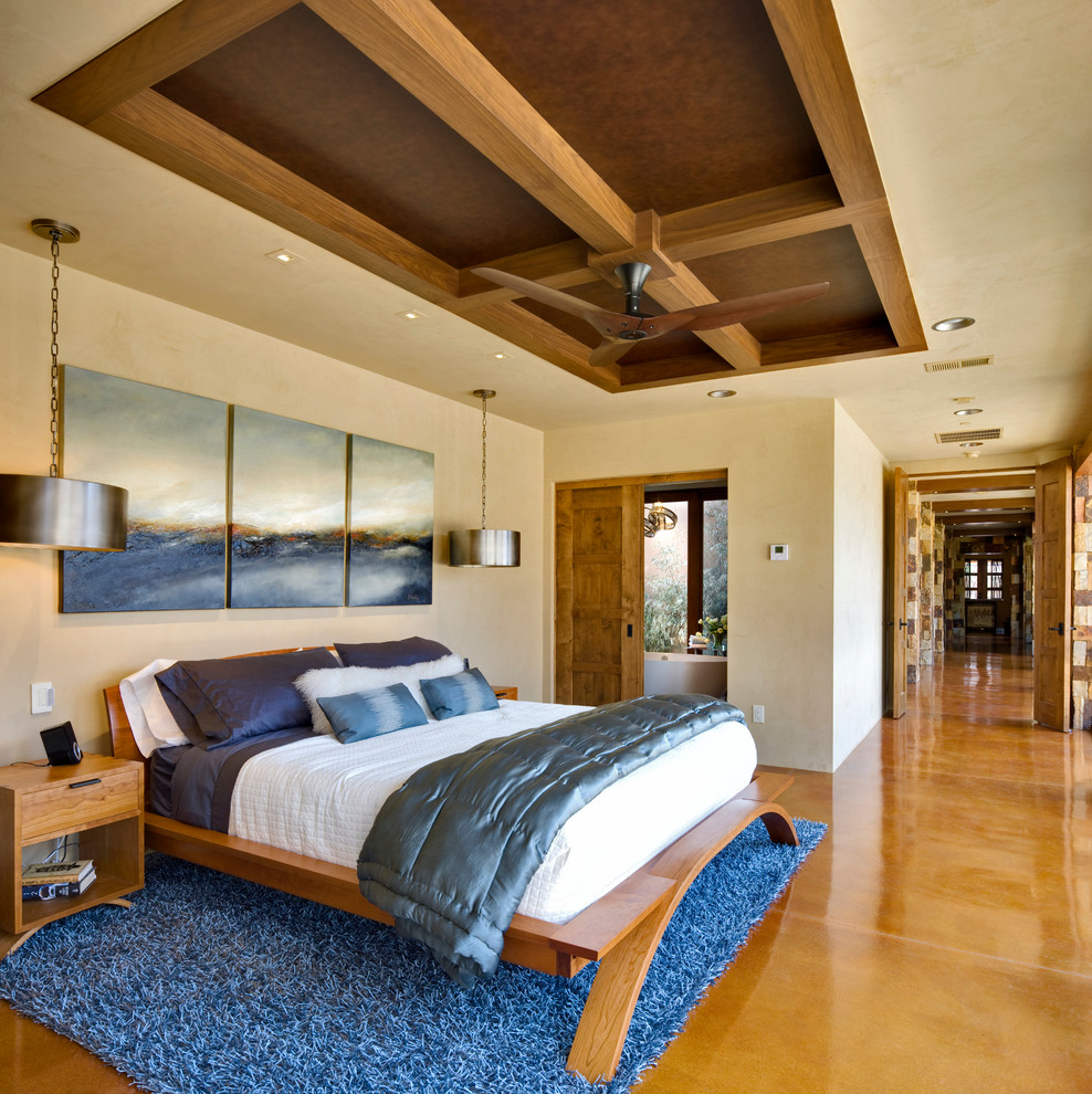 Example of a large trendy master concrete floor and yellow floor bedroom design in Albuquerque with beige walls and no fireplace