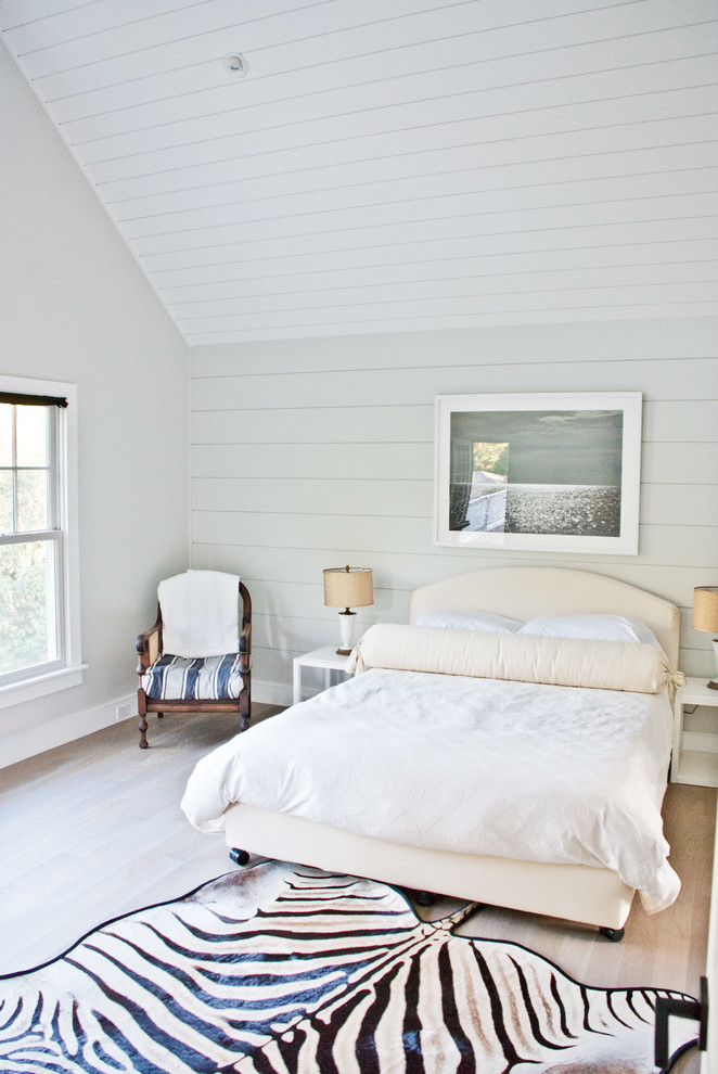 Example of a cottage light wood floor bedroom design in New York with white walls