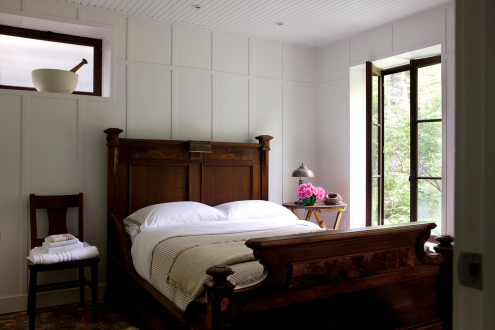 Example of a mountain style guest dark wood floor bedroom design in Montreal with white walls and no fireplace