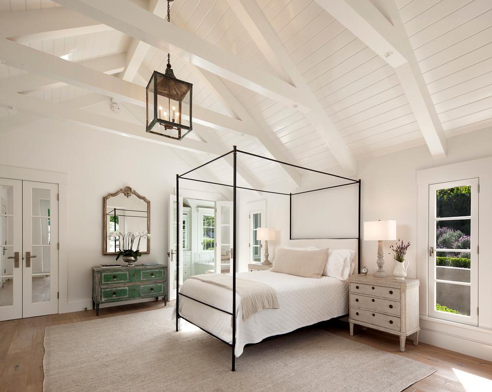 Bedroom - country master light wood floor bedroom idea in Santa Barbara with white walls