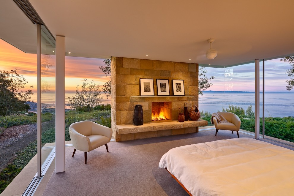 Inspiration for a modern carpeted bedroom remodel in Santa Barbara with a standard fireplace and a stone fireplace